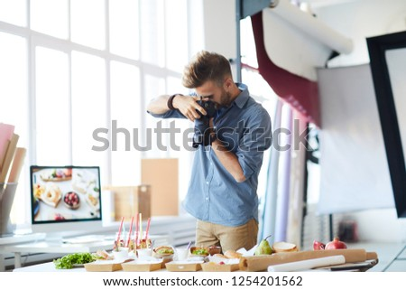 Portrait of male photographer doing food-photography while working in studio, copy space