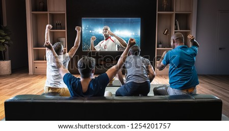 Group of students are watching a soccer moment on the TV and celebrating a goal, sitting on the couch in the living room. The living room is made in 3D. #1254201757