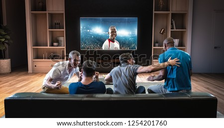 Group of students are watching a soccer moment on the TV and celebrating a goal, sitting on the couch in the living room. The living room is made in 3D. #1254201760