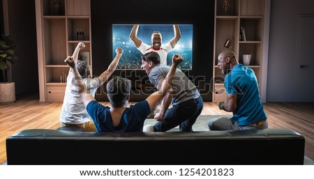 Group of students are watching a soccer moment on the TV and celebrating a goal, sitting on the couch in the living room. The living room is made in 3D. #1254201823