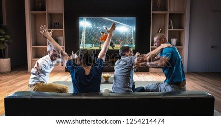 Group of students are watching a soccer moment on the TV and celebrating a goal, sitting on the couch in the living room. The living room is made in 3D. #1254214474