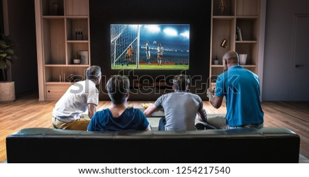 Group of students are watching a soccer moment on the TV and celebrating a goal, sitting on the couch in the living room. The living room is made in 3D. #1254217540