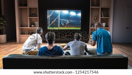 Group of students are watching a soccer moment on the TV and celebrating a goal, sitting on the couch in the living room. The living room is made in 3D. #1254217546