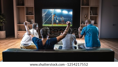Group of students are watching a soccer moment on the TV and celebrating a goal, sitting on the couch in the living room. The living room is made in 3D. #1254217552