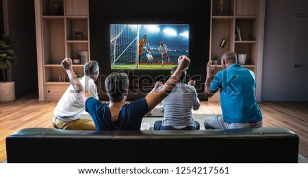Group of students are watching a soccer moment on the TV and celebrating a goal, sitting on the couch in the living room. The living room is made in 3D. #1254217561