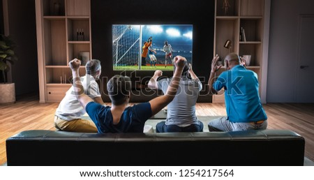 Group of students are watching a soccer moment on the TV and celebrating a goal, sitting on the couch in the living room. The living room is made in 3D. #1254217564
