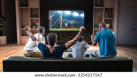 Group of students are watching a soccer moment on the TV and celebrating a goal, sitting on the couch in the living room. The living room is made in 3D. #1254217567