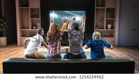 Group of students are watching a soccer moment on the TV and celebrating a goal, sitting on the couch in the living room. The living room is made in 3D. #1254224962