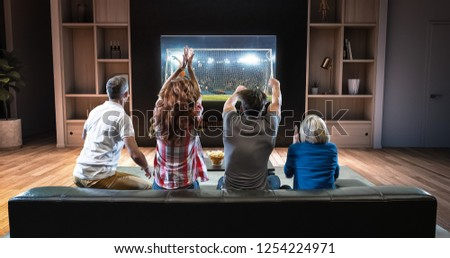 Group of students are watching a soccer moment on the TV and celebrating a goal, sitting on the couch in the living room. The living room is made in 3D. #1254224971