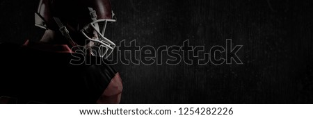 American football player in helmet looking off to the side against full frame shot of black patterned wall #1254282226