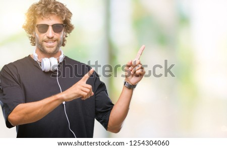 Handsome hispanic man listening to music wearing headphones over isolated background smiling and looking at the camera pointing with two hands and fingers to the side. #1254304060