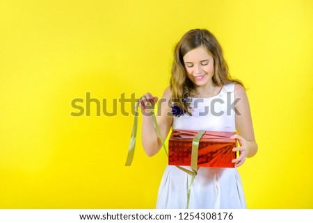 beautiful girl in white dress unties the ribbon and opens the gift, on yellow background #1254308176