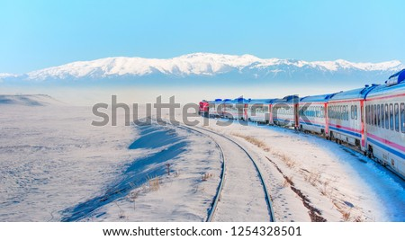 Red diesel train (East express) in motion at the snow covered railway platform - The train connecting Ankara to Kars - Turkey    #1254328501