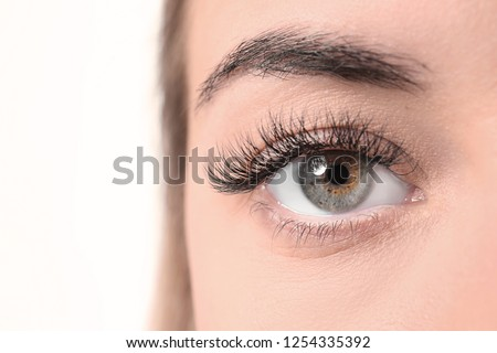 Beautiful young woman with eyelash extensions on white background, closeup #1254335392