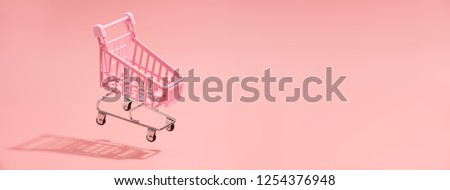 Shopping trolley on pink background Royalty-Free Stock Photo #1254376948