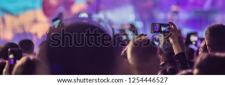 Use advanced mobile recording, fun concerts and beautiful lighting, Candid image of crowd at rock concert, Close up of recording video with smartphone, Enjoy the use of mobile photography BANNER, LONG #1254446527