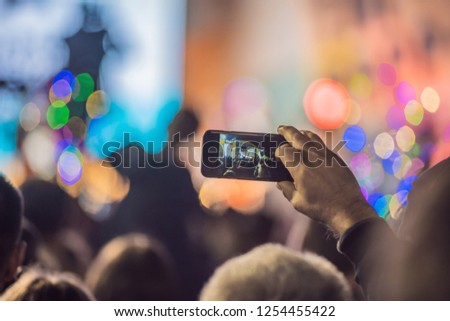 Use advanced mobile recording, fun concerts and beautiful lighting, Candid image of crowd at rock concert, Close up of recording video with smartphone, Enjoy the use of mobile photography #1254455422