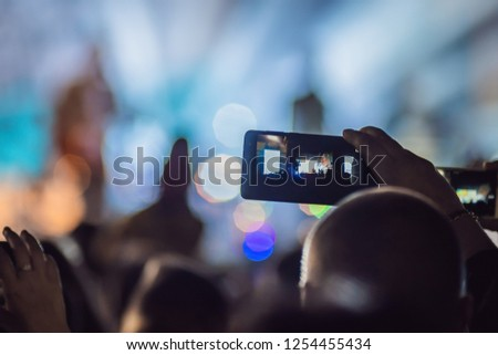 Use advanced mobile recording, fun concerts and beautiful lighting, Candid image of crowd at rock concert, Close up of recording video with smartphone, Enjoy the use of mobile photography #1254455434