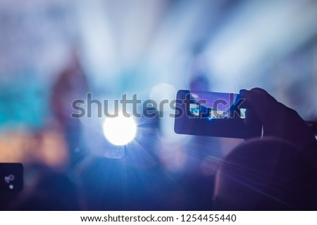 Use advanced mobile recording, fun concerts and beautiful lighting, Candid image of crowd at rock concert, Close up of recording video with smartphone, Enjoy the use of mobile photography #1254455440