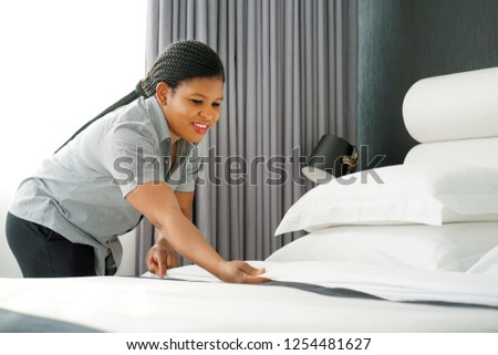 Maid making bed in hotel room. Staff Maid Making Bed. African housekeeper making bed. #1254481627