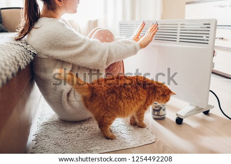 Using heater at home in winter. Woman warming her hands with cat. Heating season. #1254492208