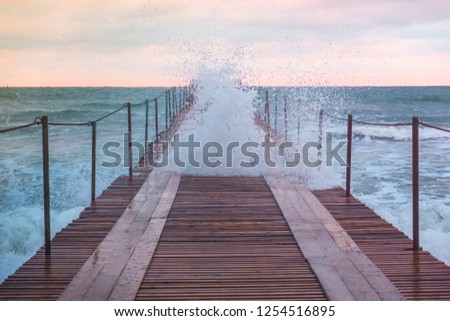 Big stormy waves in the sea through wooden pier. Beautiful seascape with pier. #1254516895