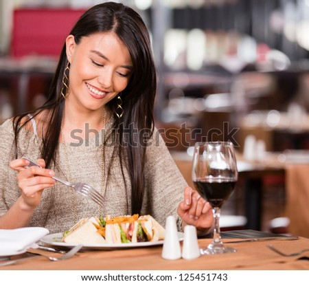 Woman eating at a restaurant looking very happy #125451743