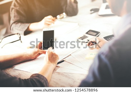 woman hand phone with team work in office table #1254578896