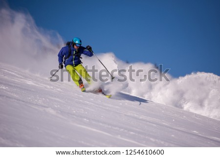 young athlete freestyle Skier having fun while running downhill in beautiful Alpine landscape on sunny day during winter season #1254610600