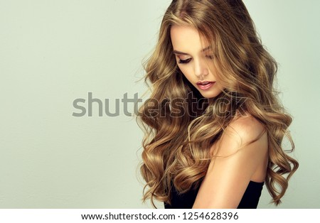 Laughing blonde girl with long  and   shiny wavy hair .  Beautiful  smiling woman model with curly hairstyle . #1254628396