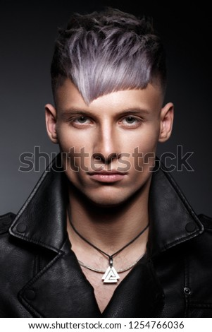 young man with purple hair and creative makeup and hair. Photo taken in the studio