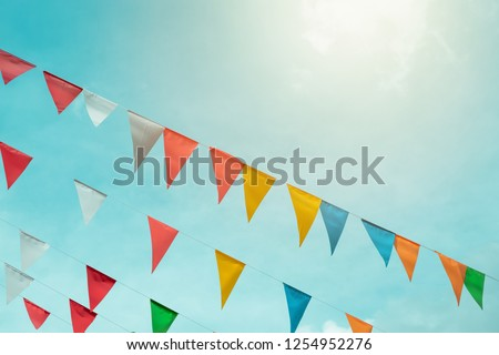 Fair flag bunting colorful background hanging on blue sky for fun fiesta party event, summer holiday farm feast celebration, carnival festival event, park or street festa design decoration #1254952276