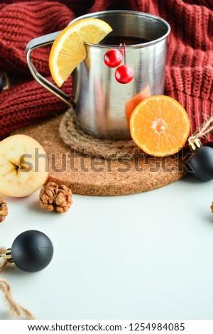 Hot lemon tea in an aluminum mug. Cozy winter red sweater.  #1254984085