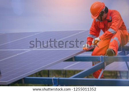 Electrical and instrument technician use wrench to maintenance electric system at solar panel field #1255011352