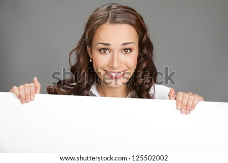Happy smiling young business woman showing blank signboard, over grey background #125502002
