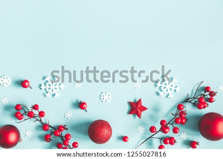 Christmas or winter composition. Frame made of snowflakes, balls and red berries on pastel blue background. Christmas, winter, new year concept. Flat lay, top view, copy space #1255027816