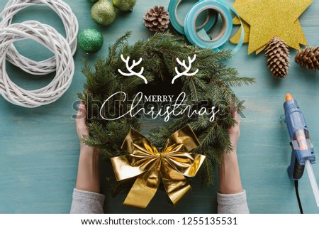 "cropped shot of woman holding handmade pine tree wreath with golden bow and decorations on blue wooden tabletop with ""merry christmas"" lettering #1255135531"