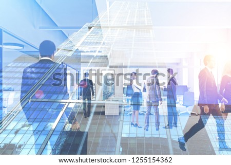Business people walking and talking in modern open space office interior with double exposure of skyscraper. Corporate lifestyle concept. Toned image #1255154362