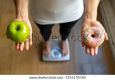 Close up of woman on scale holding on hands apple and doughnut making choice between healthy unhealthy food dessert while measuring body weight in Nutrition Health care Diet and temptation concept. #1255170760