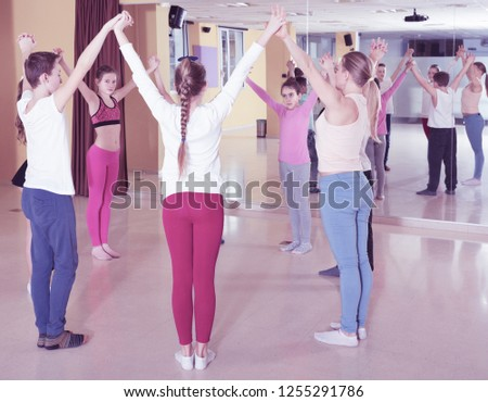 Smiling teenage boys and girls practicing circle dance with female trainer in dance hall #1255291786