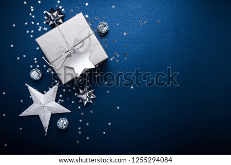 Merry Christmas and Happy Holidays greeting card, frame, banner. New Year. Noel. Silver Christmas gifts, ornaments on blue background top view. Winter holiday xmas theme. Flat lay. #1255294084