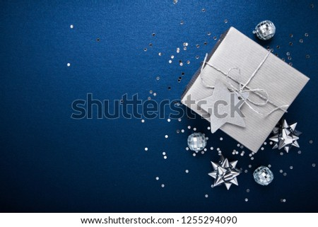 Merry Christmas and Happy Holidays greeting card, frame, banner. New Year. Noel. Silver Christmas gifts, ornaments on blue background top view. Winter holiday xmas theme. Flat lay. #1255294090