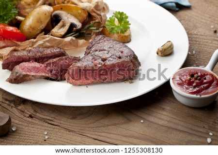 Overhead view of delicious,grilled beef steak with roasted potatoes and fresh green herb salad on an old wooden table #1255308130