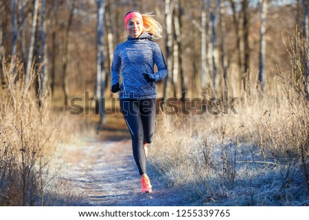 Young slim girl running in the park in early winter. Attractive woman jogging on snowy trail #1255339765