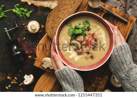 Bowl of mushroom cream soup in woman hands in a woolen sweater. Rustic dark background, top view, flat lay. Winter warming soup on vintage cutting boards #1255447351