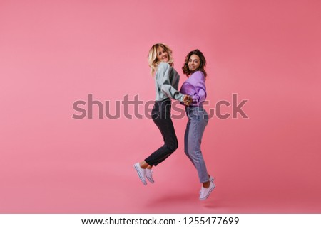 Debonair shapely girls holding hands and smiling. Studio portrait of jumping female friends expressing happiness. #1255477699