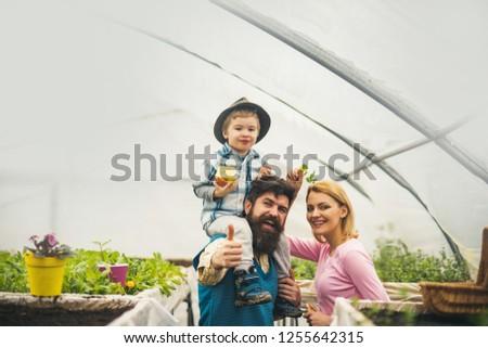 happy childhood. happy childhood concept. happy childhood of little boy with parents. happy childhood in greenhouse. gardeners #1255642315