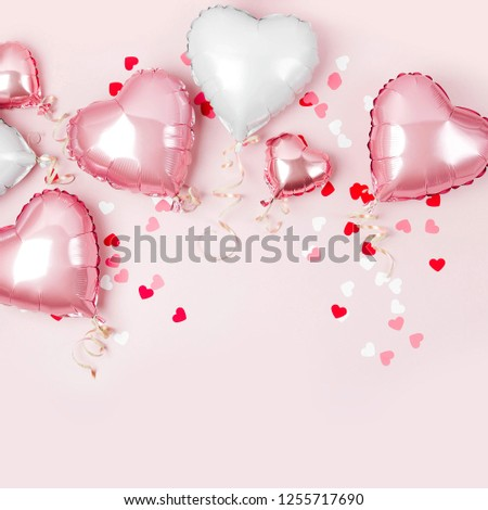 Air Balloons of heart shaped foil  on pastel pink background. Love concept. Holiday celebration. Valentine's Day or wedding/bachelorette party decoration. Metallic balloon #1255717690