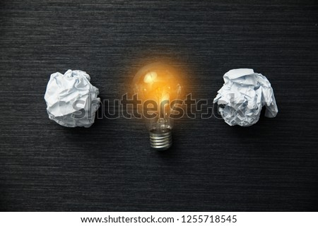 Light bulb with crumpled papers on table #1255718545