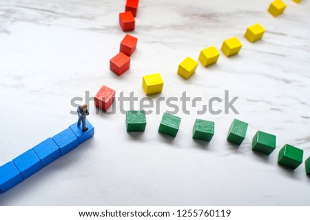 Miniature businessmen trying to pick the path to success down three different wooden block roads #1255760119